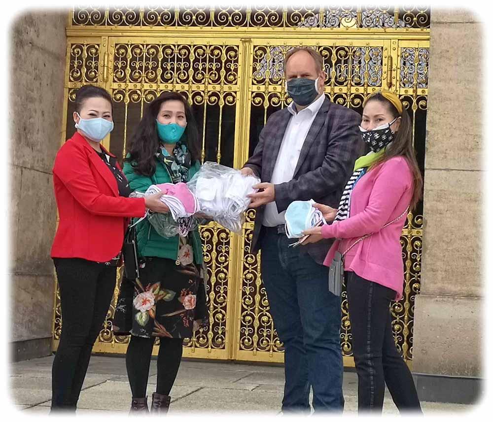 Nguyen Thi Dung (links), Bui Thu Hien und Dang Bich Lan (rechts) übergeben eine Charge von rund 50 Anti-Corona-Masken an den Dresdner Oberbürgermeister Dirk Hilbert. Foto: Heiko Weckbrodt