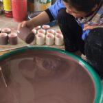 Eine Frau taucht einen Becher in braune Farbe. Blick in die Keramikmanufaktur in Bat Trang. Foto: Heiko Weckbrodt