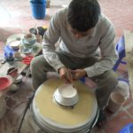 Ein Handwerker bemalt eine Schale in der Keramikmanufaktur in Bat Trang. Foto: Heiko Weckbrodt