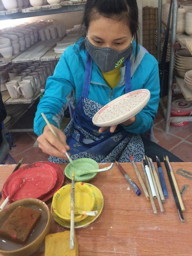 Eine Mitarbeiterin bemalt in der Keramikmanufaktur in Bat Trang eine Schale. Foto: Heiko Weckbrodt
