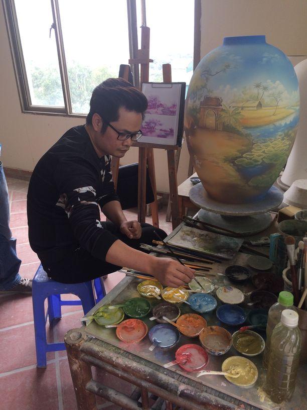 Ein Künstler bemalt in der Keramikmanufaktur in Bat Trang eine Vase. Foto: Heiko Weckbrodt