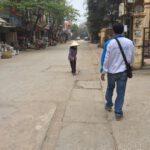 Alte Frau mit Reishut auf einer Straße in Bat Trang. Foto: Heiko Weckbrodt